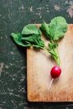 Radish on a wooden board / background. Radish on a wooden board and green background Royalty Free Stock Photo