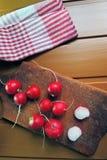 Radish on wooden Board. Large bunch of fresh radish on dark boards, closeup Stock Image