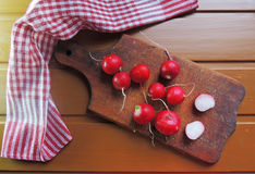 Radish on wooden Board. Large bunch of fresh radish on dark boards, closeup Royalty Free Stock Image