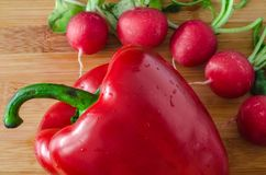 Radishes around of red sweet pepper in drops. On bright wooden background, top view Stock Photography