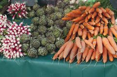 Radishes, artichokes and carrots on the market. Radishes, artichokes and carrots for sale on the market Stock Photography