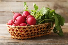 Radishes in basket. Red radishes in basket on grey wooden table Stock Photography