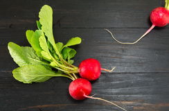 Radishes on a black table. Red whole radishes on a black table Stock Photo
