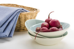 Radishes in a Blue Bowl. With blue denim napkins and a wicker basket against a white background Royalty Free Stock Photos