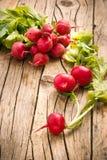 Radishes. Bunch of fresh red radishes on wooden background Stock Image