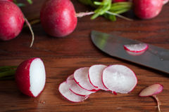 Radishes on a Cutting Board. Fresh radishes sliced on a wooden cutting board with a knife Royalty Free Stock Photos