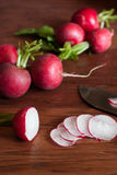 Radishes on a Cutting Board. Fresh radishes sliced on a wooden cutting board with a knife Stock Photo