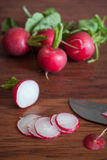 Radishes on a Cutting Board. Fresh radishes sliced on a wooden cutting board with a knife Stock Image