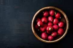 Radishes Filling Old Wooden Bowl on Grungy Black Surface from Ab Royalty Free Stock Image
