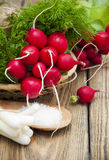 Radishes. Fresh radishes in a basket with green onions and salt on a wooden background Royalty Free Stock Photos