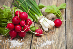 Radishes. Fresh radishes with green onions and salt on a wooden background Royalty Free Stock Photo