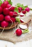 Radishes. Fresh radishes with salt on a wooden background Royalty Free Stock Photos