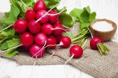 Radishes. Fresh radishes with salt on a wooden background Royalty Free Stock Photography