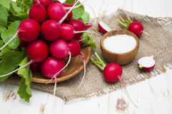 Radishes. Fresh radishes with salt on a wooden background Stock Photography