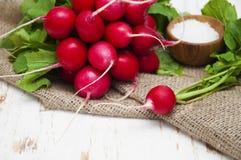 Radishes. Fresh radishes with salt on a wooden background Royalty Free Stock Image