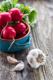 Radishes and Garlic. Bunch of radishes in a vintage bowl and garlic on a old wooden table Stock Photography