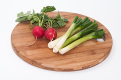 Radishes and green onions washed and placed on a wooden board.  Royalty Free Stock Images