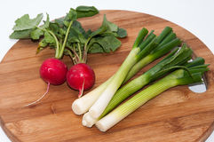 Radishes and green onions washed and placed on a wooden board.  Stock Photos