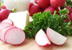 Radishes. Ingredients for radish spread or radish soup - radishes, butter, cream and green parsley. Wooden background. Closeup view Royalty Free Stock Photos