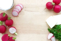 Radishes. Ingredients for radish spread or radish soup - radishes, butter, cream and green parsley. Wooden background. Top view Stock Image