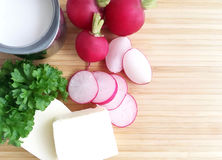 Radishes. Ingredients for radish spread or radish soup - radishes, butter, cream and green parsley. Wooden background. Top view Royalty Free Stock Photo