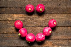 Radishes laid out in the shape of a smile on wooden table. Red, raw, whole radishes laid out in the shape of a smile on dark brown wooden table. Top view stock image