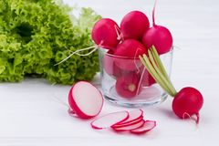 Radishes and lettuce on white background. Whole and sliced radishes close up. Fresh green lettuce. Eat better and feel better Stock Images
