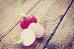Radishes on old wooden board,tinted. Fresh, juicy radishes on old wooden board Stock Image