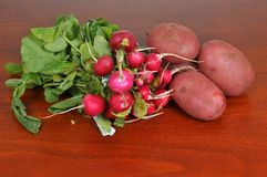 Radishes and potatoes. Fresh radishes and potatoes on a wooden board Royalty Free Stock Images