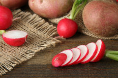 Radishes. Red potatoes with chopped radishes on sackcloth on wooden brown background Royalty Free Stock Image