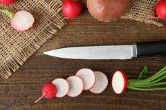 Radishes. Red potatoes with chopped radishes on sackcloth on wooden brown background with a knife Royalty Free Stock Images