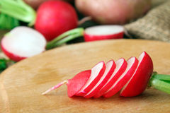 Radishes. Red potatoes on wooden brown background near a cutting Board with sliced radishes on wooden brown background Royalty Free Stock Photos