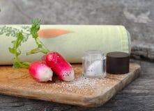 Radishes in salt. Fresh radishes on salt on a wooden plank Stock Images