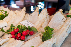 Radishes and on stockfish. Radishes and parsley laid on stockfish in a fishmarket Stock Images