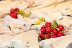 Radishes and on stockfish. Radishes and parsley laid on stockfish in a fishmarket Royalty Free Stock Image