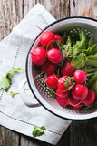 Radishes in white colander. Top view on fresh wet radishes in white colander over old wooden table Royalty Free Stock Photos