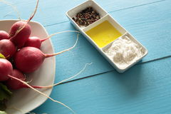 Radishes on a white plate. On wooden background Royalty Free Stock Images
