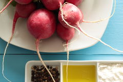 Radishes on a white plate. On wooden background Stock Photography