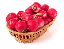 Radishes in a wicker basket isolated on white background.  Royalty Free Stock Images
