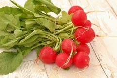 Radishes on the wooden background. Front horizontal view Royalty Free Stock Images