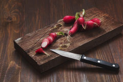 Radishes. On a wooden cutting Board on a rustic wooden table Stock Photo
