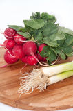 Radishes and young onions on a kitchen wooden board.  Royalty Free Stock Photography
