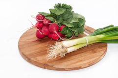Radishes and young onions on a kitchen wooden board.  Royalty Free Stock Photo
