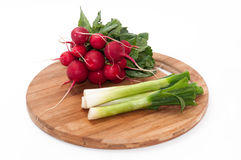 Radishes and young onions on a kitchen wooden board.  Stock Image