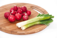 Radishes and young onions on the kitchen wooden board Royalty Free Stock Photo