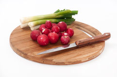 Radishes and young onions and knife on the kitchen wooden board.  Royalty Free Stock Images
