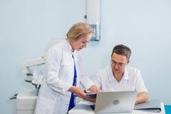 Radośni ogólni lekarzi praktykujący dyskutuje ich pracę przy szpitalnym biurem Obraz Stock