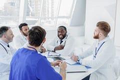 Radośni ogólni lekarzi praktykujący opowiada w klinice Fotografia Royalty Free