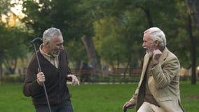 Radośni przechodzić na emeryturę mężczyźni tanczy parka z chodzącymi kijami wpólnie, mieć zabawę, humor zbiory