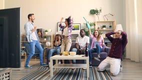 Radośni ucznie ogląda futbol na TV w mieszkanie odświętności zwycięstwie zdjęcie wideo